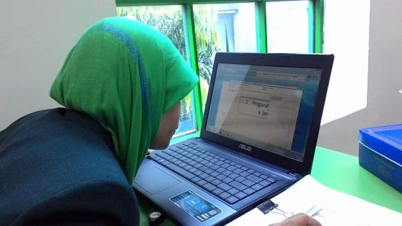 Bu Odah sedang membaca tulisan di laptop